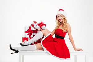 Smiling beautiful young woman in santa claus costume sitting and holding present boxes