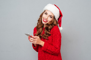 Smiling beautiful young woman in santa claus hat using mobile phone