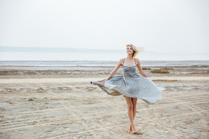 Smiling beautiful young woman standing and whirling on the beach