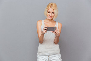Smiling beautiful young woman using cell phone over gray background
