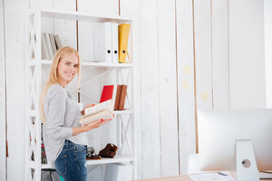 Smiling blonde business woman reading book while standing in office