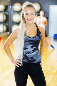 Smiling blonde fitness woman in workout outfit at the gym