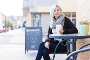 Smiling blonde woman drinking coffee outdoor at cafe