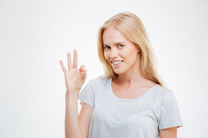 Smiling blonde woman showing ok sign isolated on a white background
