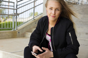 Smiling blonde woman sits outdoor and uses phone