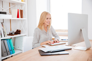 Smiling blonde woman sitting at her workplace and working on computer