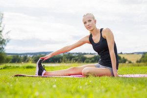 Smiling blonde woman stretching outdoor on the grass
