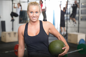 Smiling blonde woman with slam ball