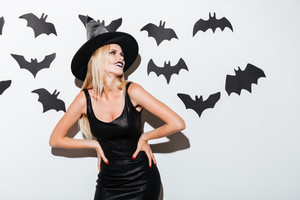 Smiling blonde young woman in witch costume with hat standing over white background