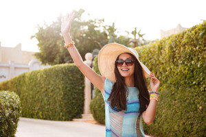 Smiling Brunette Woman in beachwear which posing near the bushes and waving away