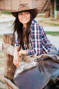 Smiling brunette young woman cowgirl leaning on fence in village and looking away