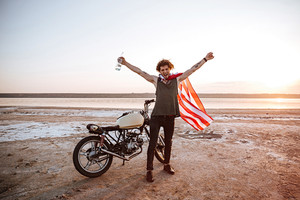 Smiling brutal man in american flag cape sitting on his motocycle with hands up in the air