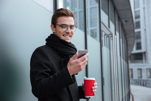 Smiling Business man in glasses and warm clothes with coffee and phone outdoors