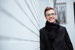 Smiling business man in glasses, coat and scarf standing near the wall of house