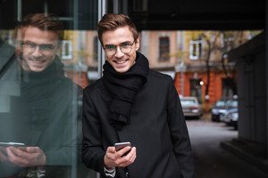 Smiling business man in glasses with phone near the building. looking at camera