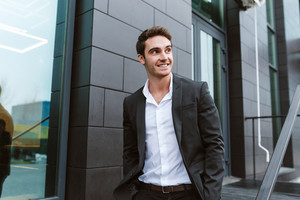 Smiling business man in suit standing near the office building and looking aside