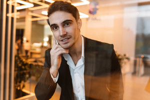 Smiling business man in suit talking on phone behind the glass in office and looking at camera