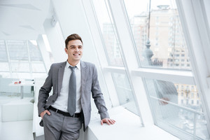 Smiling Business man standing near the window in office with arm in pocket and looking away