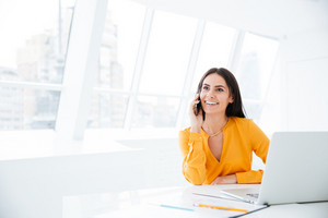Smiling Business woman talking at phone and sitting by the table in office
