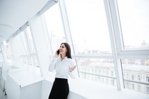 Smiling Business woman talking at phone and standing near the window in office
