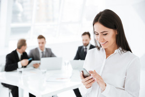 Smiling Business woman using cell phone with colleagues on background in office