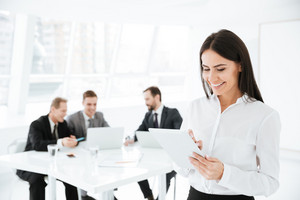 Smiling Business woman with colleagues by the table on background in office
