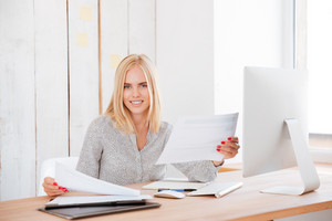 Smiling business woman working with papers and computerr in office