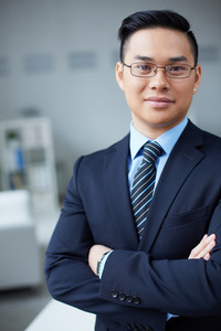 Smiling businessman in formalwear looking at camera in office