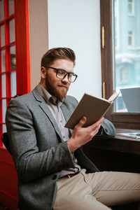 Smiling casual businessman sitting at the office and reading book