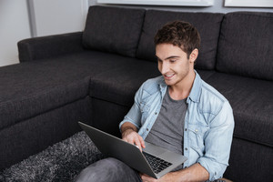 Smiling casual man sitting on carpet with laptop computer at home