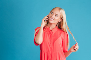 Smiling casual woman talking on the phone and looking up at copyspace over blue background