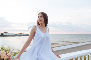 Smiling charming young woman in white dress sitting on promenade