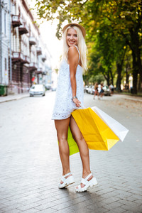 Smiling charming young woman with shopping bags walking outdoors
