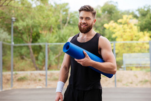 Smiling cheerful bearded fitness man with yoga mat standing outdoors