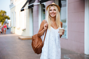 Smiling cheerful blonde girl in white dress holding take away cup outdoors