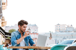 Smiling cheerful casual man using laptop while sitting at cafe outdoors and drinking coffee
