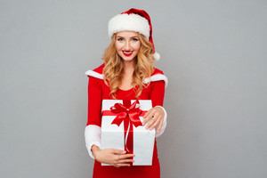 Smiling cheerful woman in red christmas outfit holding big gift box isolated on the gray background