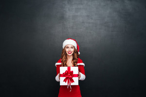 Smiling cheerful woman in red santa claus outfit holding big white box with a red ribbon isolated on the black background