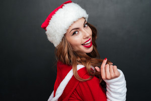 Smiling christmas girl posing over black colored background. Close up