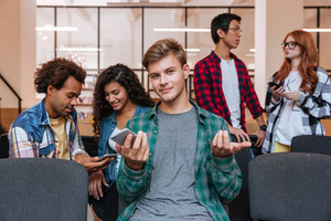 Smiling confused young man sitting and using mobile phone whie his friends talking
