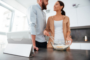 Smiling couple cooked in kitchen with tablet. eyes to eyes