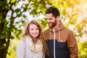 Smiling couple in love  in autumn sunny nature on a walk,  against green trees