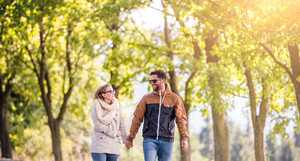 Smiling couple in love  in autumn sunny nature on a walk, holding hands, against green trees