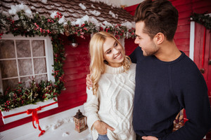 Smiling couple in sweaters near the house. eyes to eyes