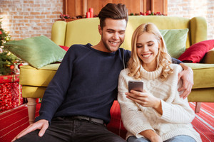 Smiling couple in sweaters sitting near the sofa and looks at phone