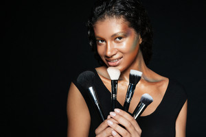 Smiling cute african american young woman with makeup brushes