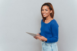Smiling cute african woman in sweater standing sideways with tablet computer in hands and looking at camera. Isolated gray background