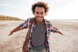 Smiling cute african young man with arms spread opened at the beach