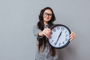 Smiling cute Asian woman in glasses and gray shirt holding clock in hands and looking at camera. Focus on clock. Isolated gray background