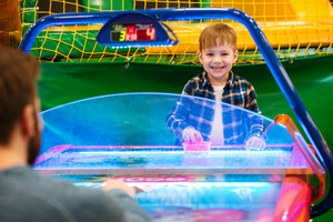 Smiling cute little boy playing air hockey with his father and having fun